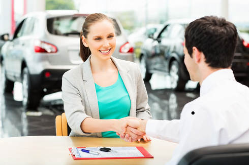 Woman signs automobile deal \\ Refinance Car Loan